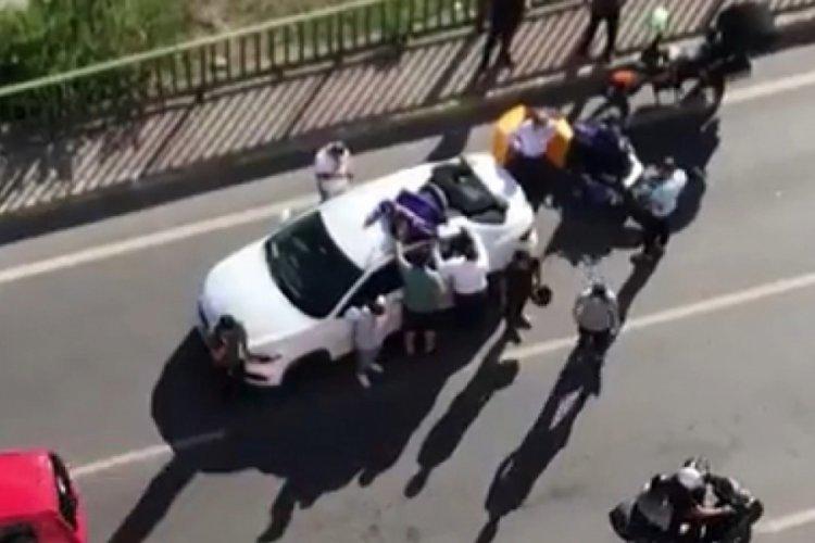 Kaza yapan motokurye otomobilin tavanına uçtu