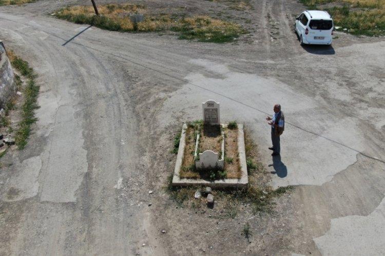 Yol ortasında kalan mezar görenleri şaşırtıyor