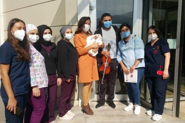 Bursa'da müzisyen baba, bebeğini hastane kapısında kemanla karşıladı